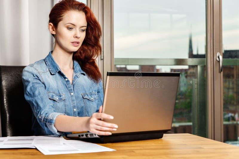 Mujer de negocios o muchacha joven pelirroja del estudiante que trabaja con los documentos y el ordenador portátil cerca de venta fotografía de archivo