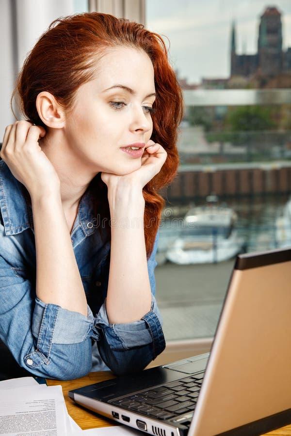 Mujer de negocios o muchacha joven pelirroja del estudiante que trabaja con los documentos y el ordenador portátil cerca de venta foto de archivo libre de regalías