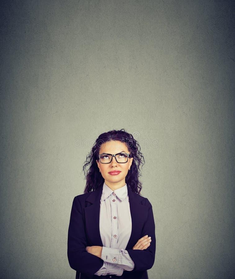 Mujer de negocios de pensamiento en los vidrios que miran para arriba imagen de archivo libre de regalías