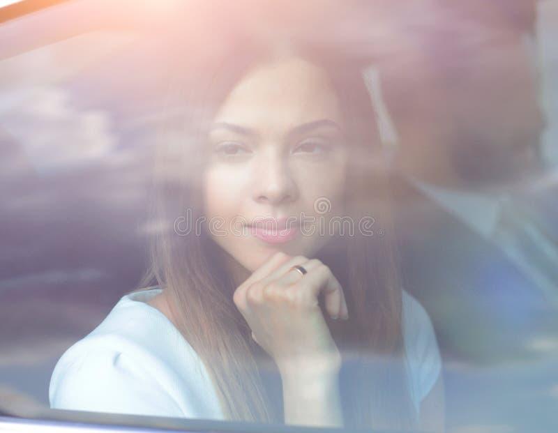 Mujer de negocios pensativa que se sienta en asiento trasero del coche foto de archivo libre de regalías