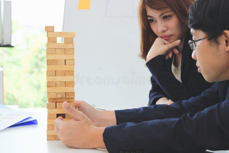 Mujer de negocios pensativa y atenta que juega la torre de madera del bloque en oficina Concepto del negocio del riesgo y de la e imagen de archivo