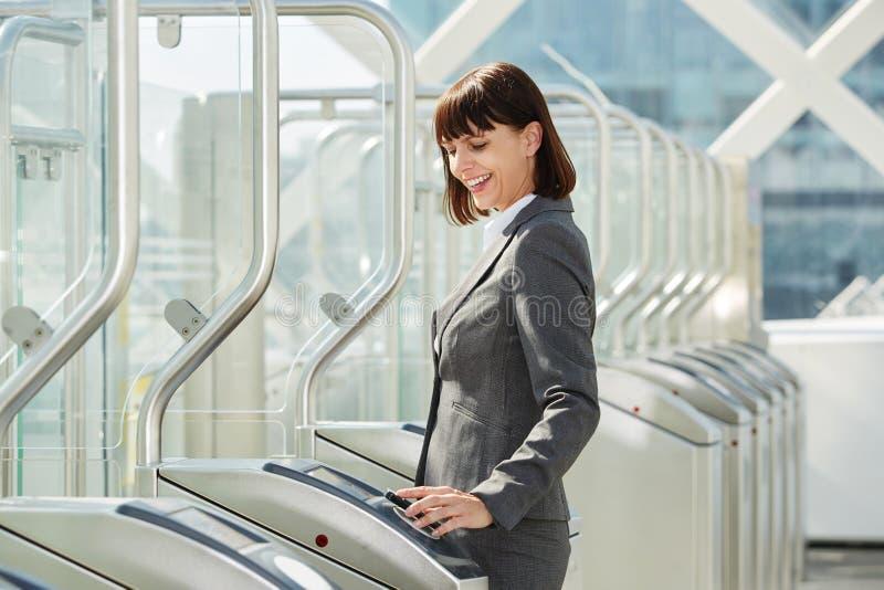 Mujer de negocios profesional que camina a través de barrera de la plataforma fotografía de archivo libre de regalías
