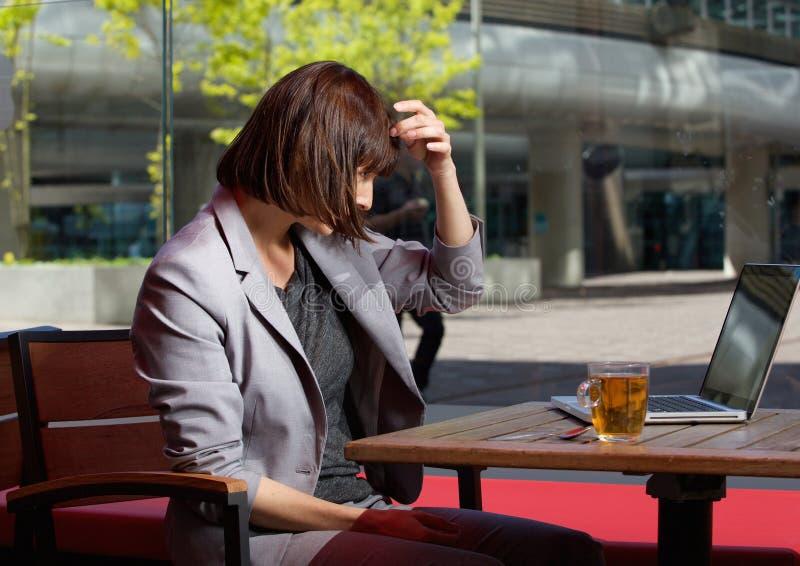Mujer de negocios que ajusta su pelo y que mira el ordenador portátil foto de archivo