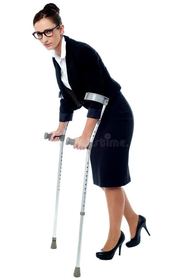 Mujer de negocios que camina con la ayuda de muletas fotografía de archivo