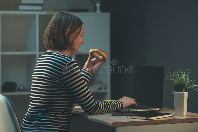 Mujer de negocios que come el bocado cocido sobre el ordenador portátil de la oficina imagen de archivo libre de regalías