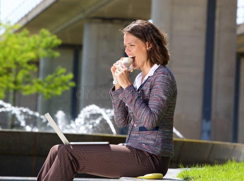 Mujer de negocios que come la comida durante hora de la almuerzo foto de archivo libre de regalías