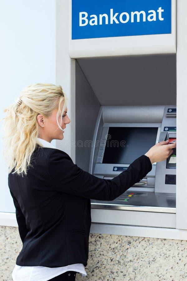 Mujer de negocios que consigue el dinero de tarjeta de crédito fotos de archivo libres de regalías