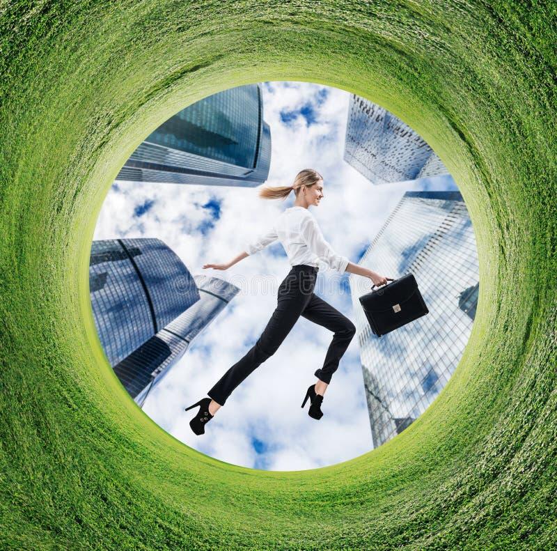 Mujer de negocios que corre en campo girado con la hierba verde fotografía de archivo