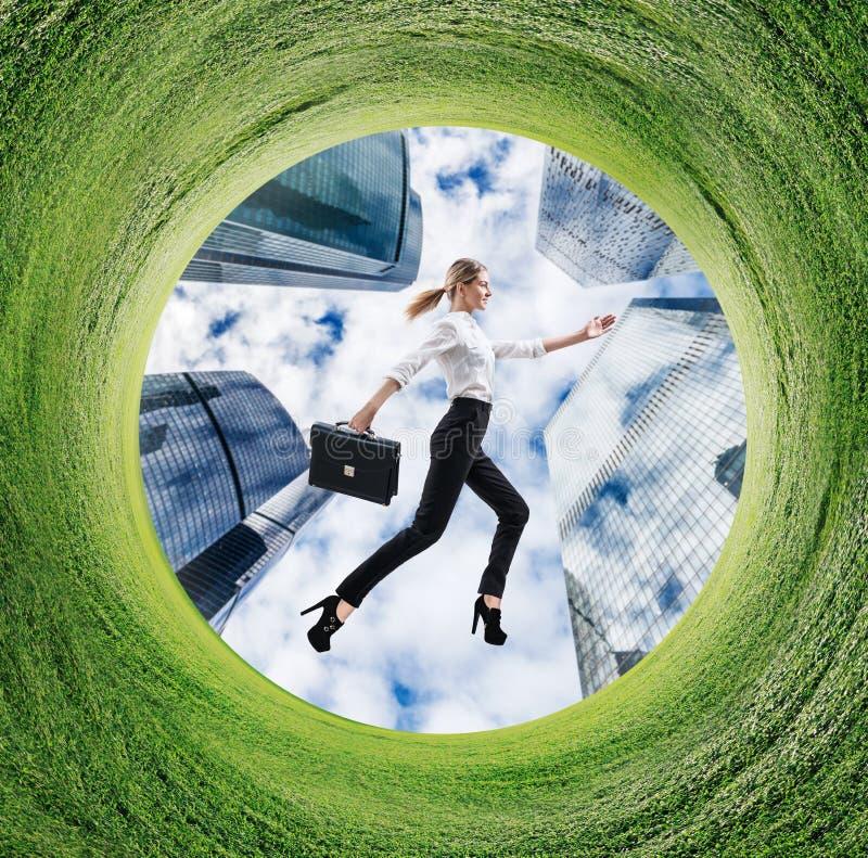 Mujer de negocios que corre en campo girado con la hierba verde imagenes de archivo