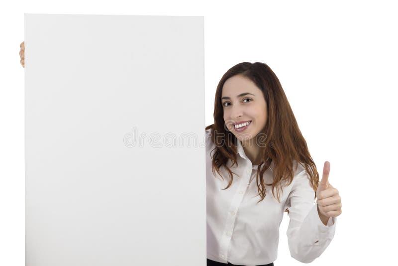 Mujer de negocios que da los pulgares para arriba y que muestra un cartel en blanco foto de archivo libre de regalías