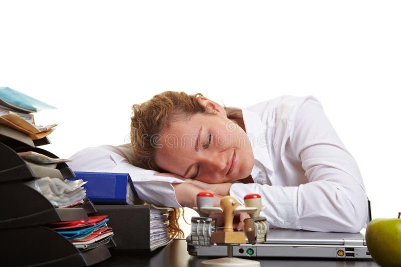Mujer de negocios que duerme en su escritorio fotografía de archivo