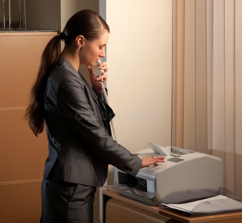 Mujer de negocios que envía el fax foto de archivo