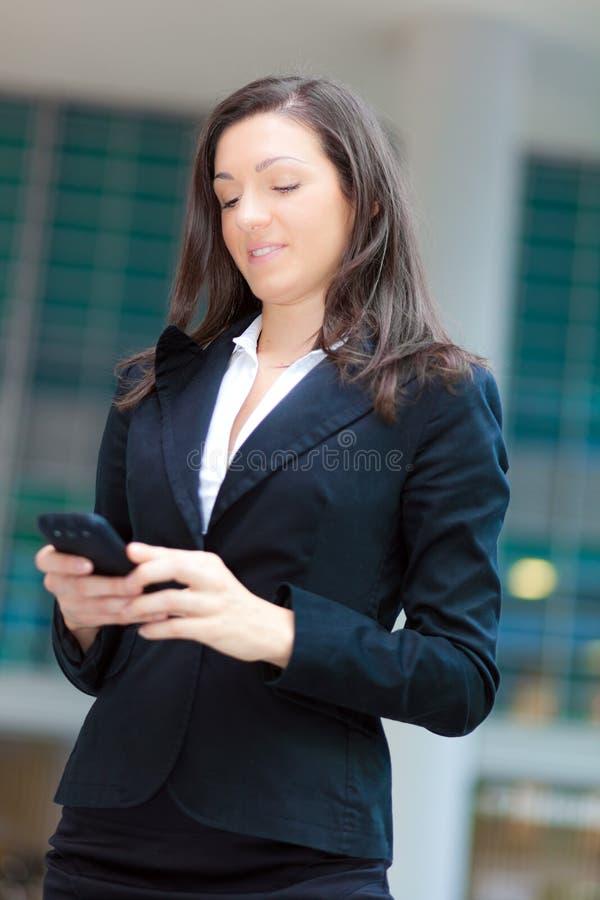 Mujer de negocios que envía el SMS al aire libre fotos de archivo libres de regalías