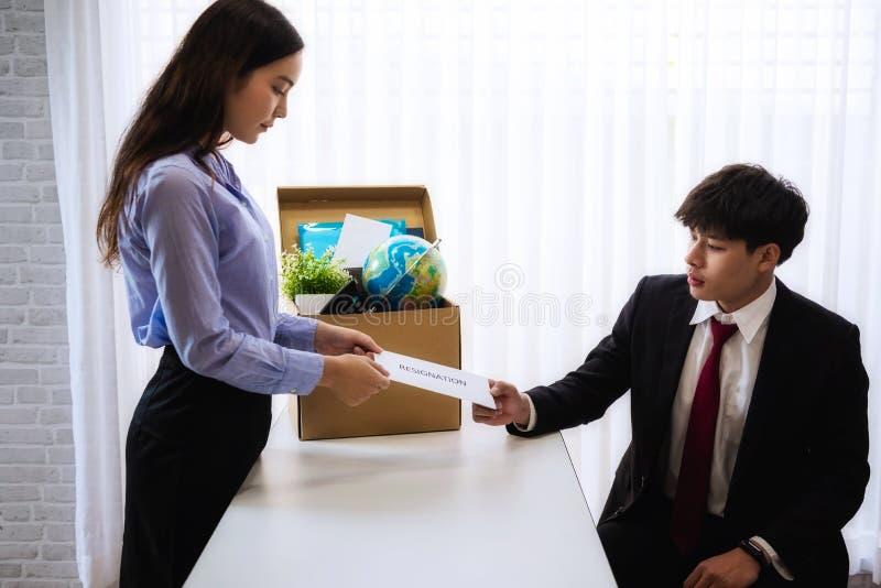 Mujer de negocios que envía la letra para la dimisión para dirigir con la caja de cartón en escritorio en la oficina El concepto  fotografía de archivo