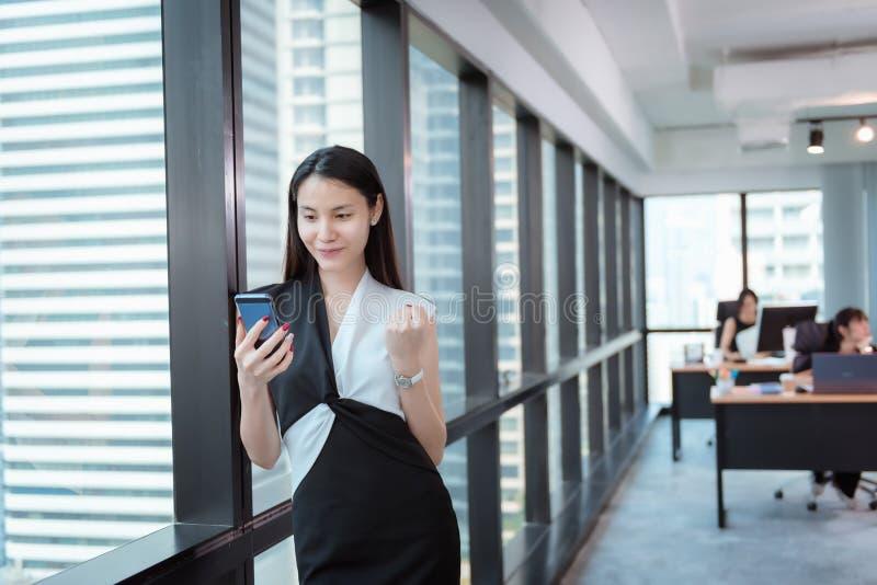Mujer de negocios que excita y feliz después de tratar del proyecto acertado mientras que usando Smartphone , Empresaria Exciting foto de archivo libre de regalías