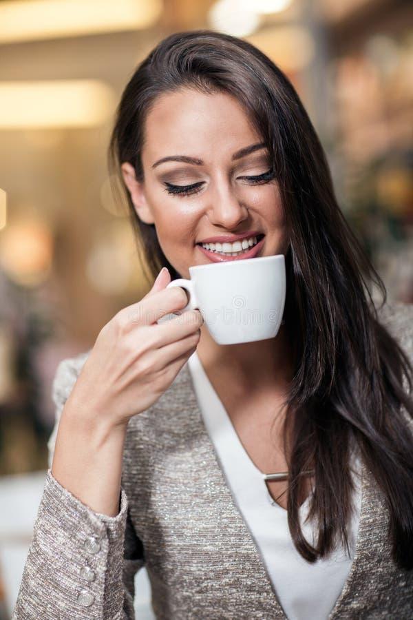 Mujer de negocios que goza del café en una barra del café imagenes de archivo