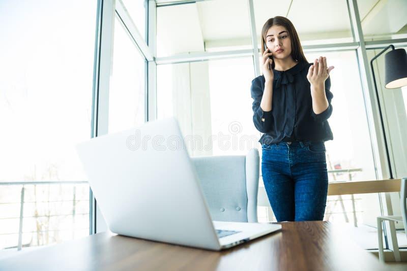 Mujer de negocios que habla en el teléfono cerca de la tabla y que mira el ordenador portátil foto de archivo libre de regalías
