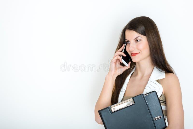 Mujer de negocios que habla en el teléfono contra un fondo blanco fotografía de archivo libre de regalías
