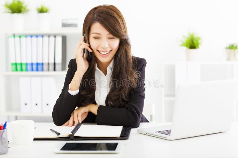 Mujer de negocios que habla en el teléfono en oficina imagen de archivo