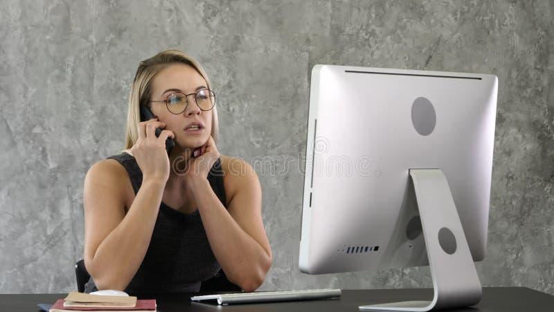Mujer de negocios que habla en el teléfono móvil que se sienta en la oficina foto de archivo libre de regalías
