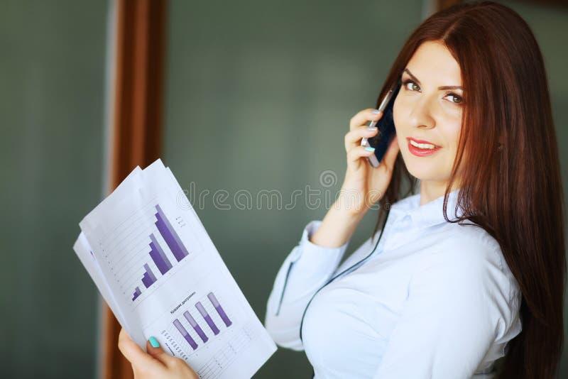 Mujer de negocios que habla en el teléfono móvil, sonriendo y mirando la cámara Profundidad del campo baja foto de archivo