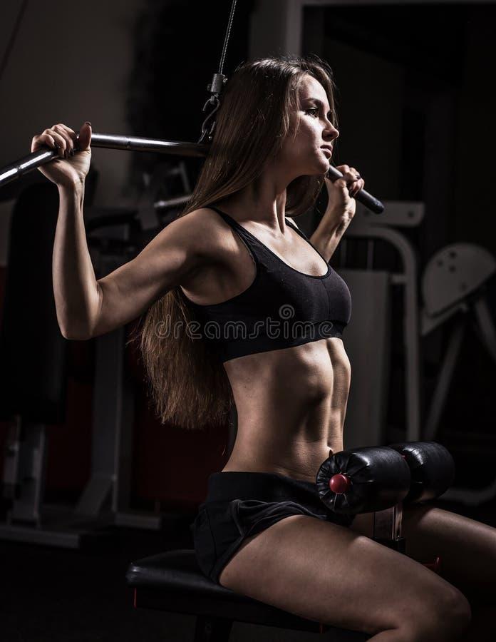 Mujer de negocios que hace ejercicio en una máquina de la aptitud en un club de fitness fotografía de archivo