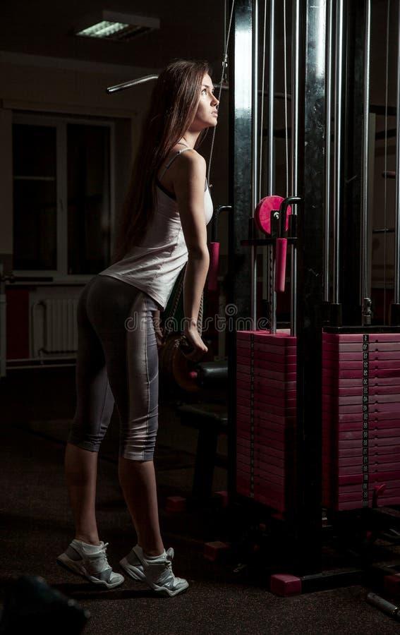 Mujer de negocios que hace ejercicio en una m?quina de la aptitud en un centro de aptitud imagen de archivo libre de regalías