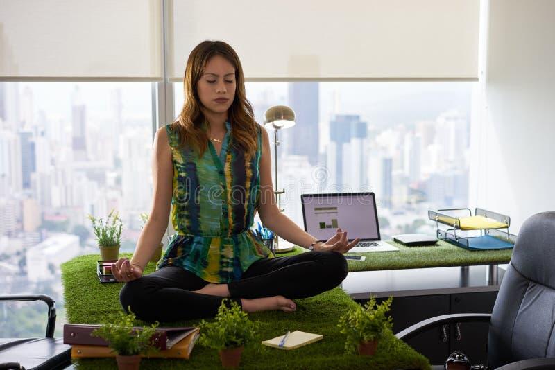 Mujer de negocios que hace la meditación de la yoga en la tabla en Office-2 imagen de archivo libre de regalías