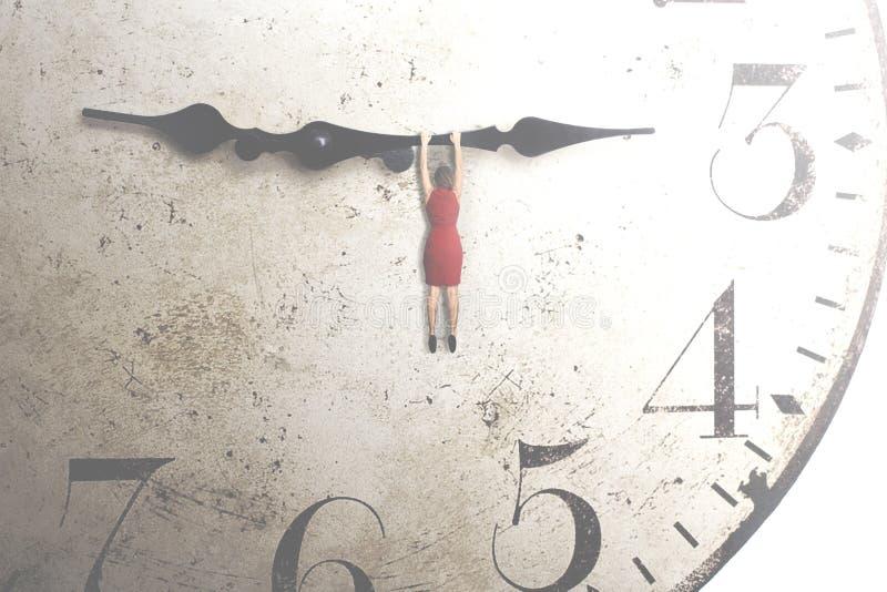 mujer de negocios que intenta parar el tiempo que cuelga en la mano de un reloj imagenes de archivo