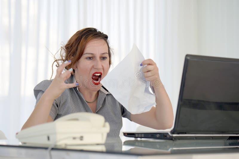 Mujer de negocios que lee un documento en espacio de trabajo de la oficina imágenes de archivo libres de regalías