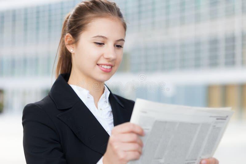 Mujer de negocios que lee un periódico fotografía de archivo
