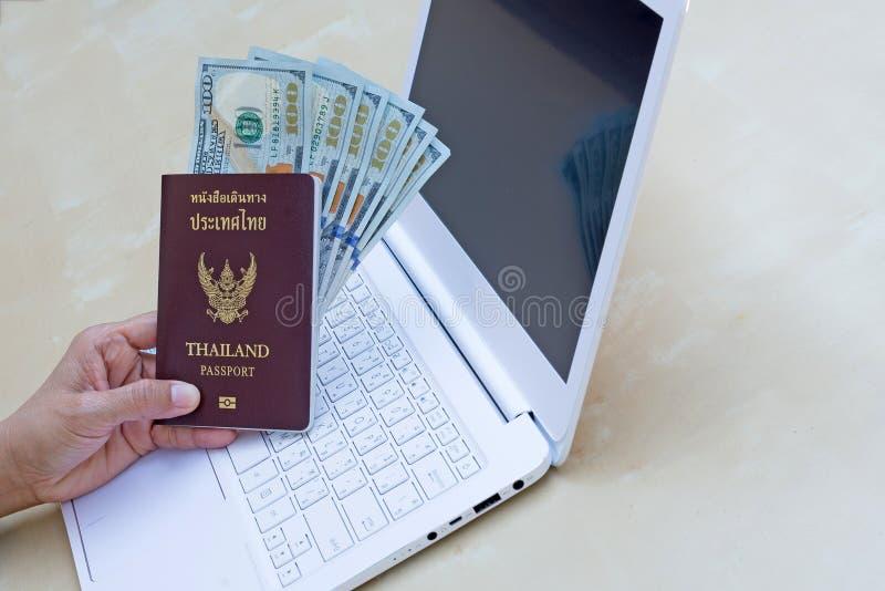 mujer de negocios que lleva a cabo el pasaporte, la moneda americana del dólar y u imagen de archivo libre de regalías
