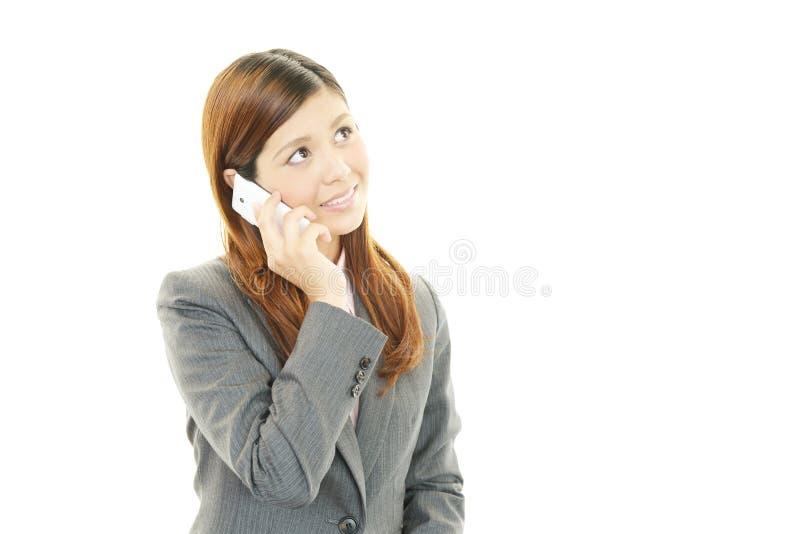 Mujer de negocios que lleva a cabo un teléfono móvil y hablar foto de archivo