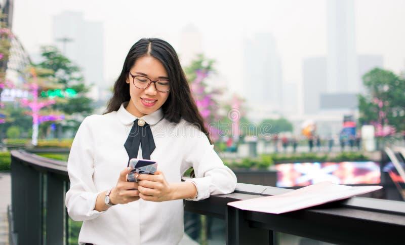 Mujer de negocios que manda un SMS en el ambiente moderno fotografía de archivo