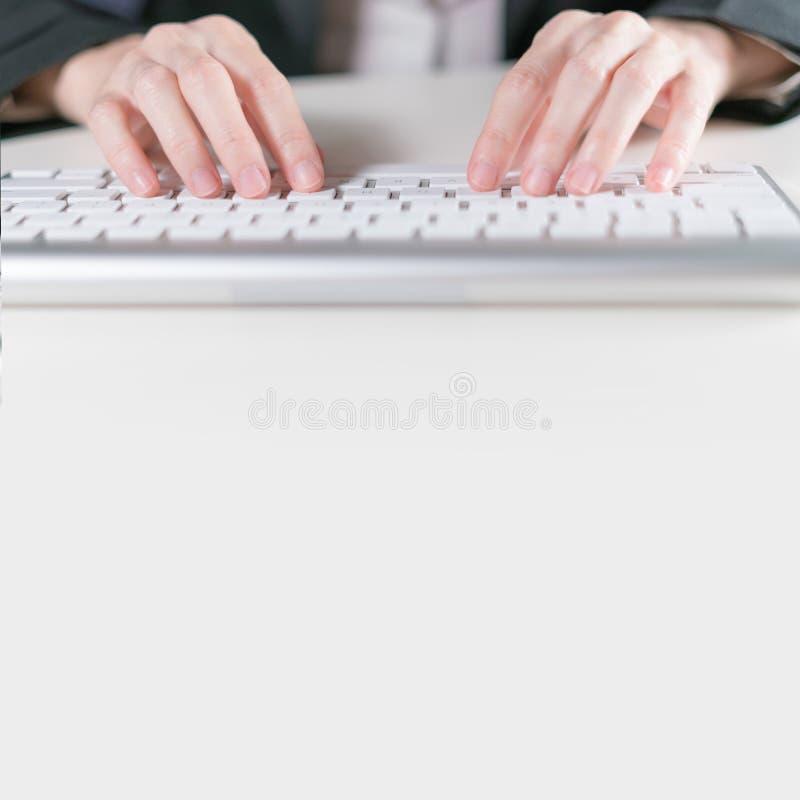 Mujer de negocios que mecanografía en el ordenador del teclado en el escritorio blanco con el copyspace imagenes de archivo