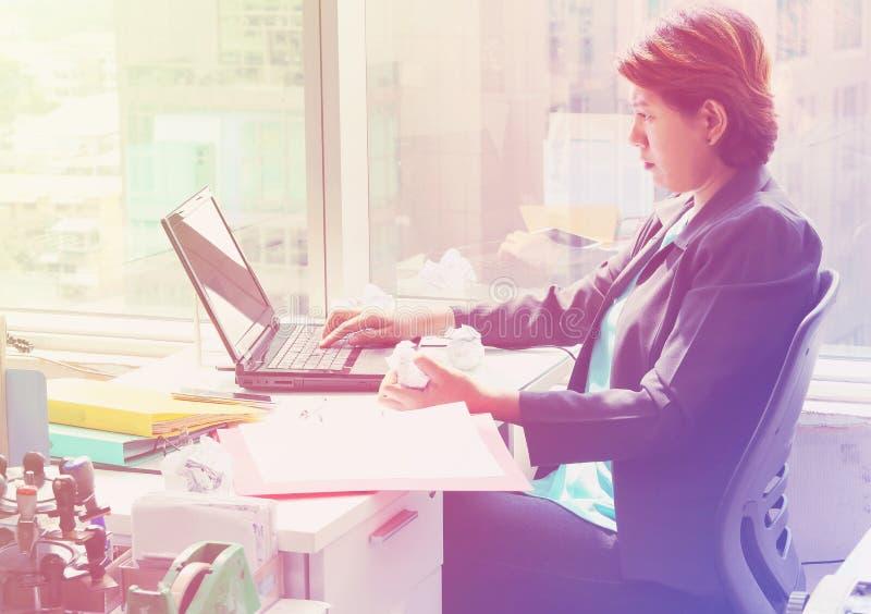Mujer de negocios que mira el ordenador portátil con la cara seria imagen de archivo libre de regalías