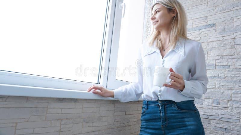 Mujer de negocios que mira hacia fuera la ventana fotos de archivo