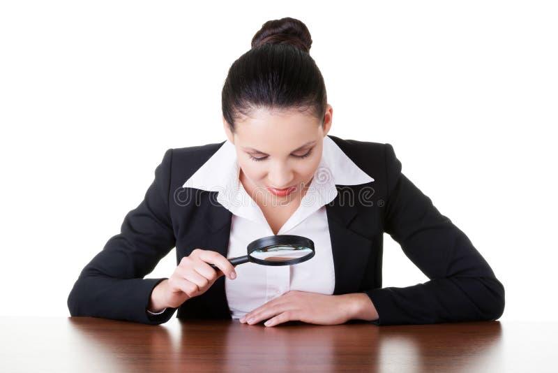 Mujer de negocios que mira a través de la lupa en la tabla. imágenes de archivo libres de regalías