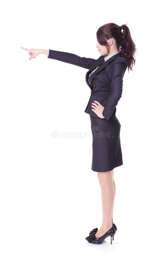Mujer de negocios que muestra el espacio de la copia por el dedo imagen de archivo