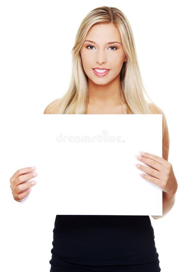 Mujer de negocios que muestra el letrero en blanco imagen de archivo