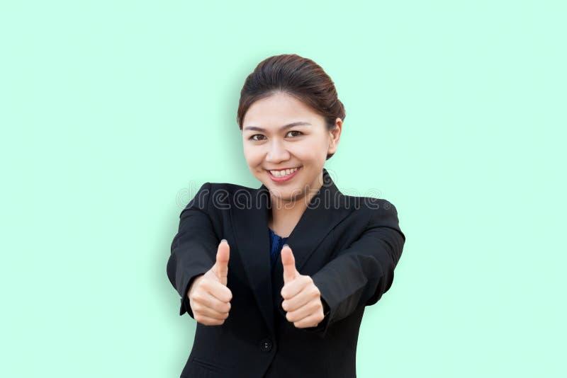 Mujer de negocios que muestra los pulgares para arriba con la sonrisa adentro imagen de archivo
