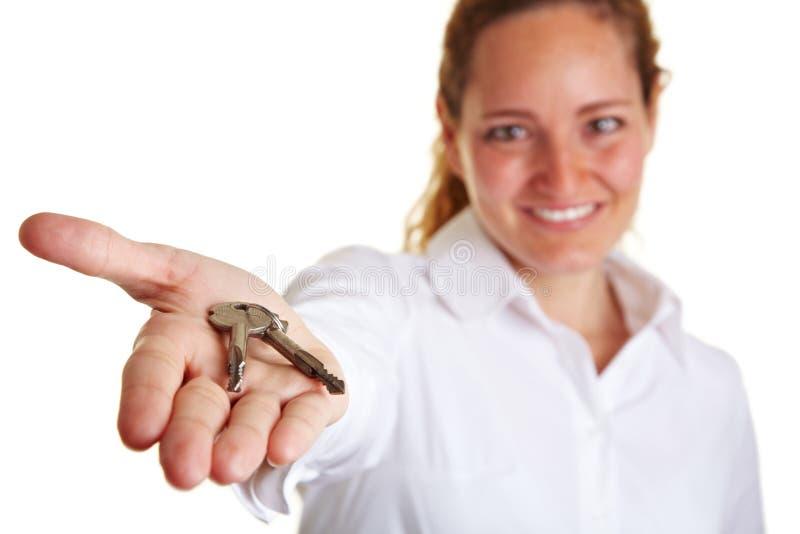 Mujer de negocios que ofrece dos claves foto de archivo