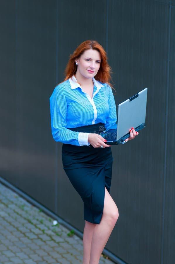Mujer de negocios que presenta con un ordenador portátil en un frente del edificio de oficinas fotografía de archivo libre de regalías