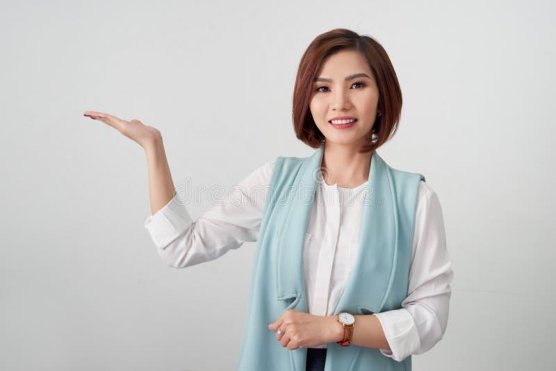 Mujer de negocios que presenta el producto en su mano aislada en blanco foto de archivo