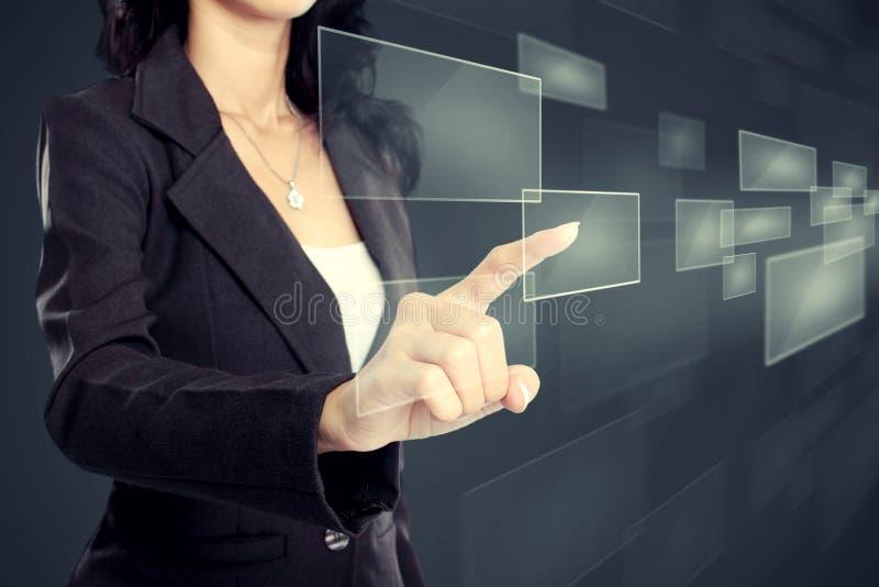 Mujer de negocios que presiona el medios botón virtual foto de archivo