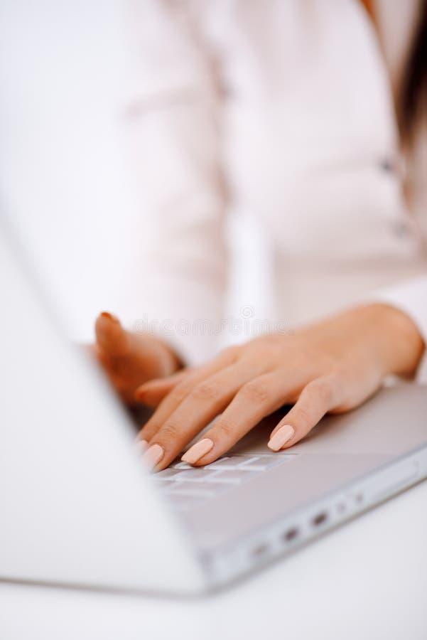 Mujer de negocios que pulsa en el teclado de la computadora portátil imágenes de archivo libres de regalías