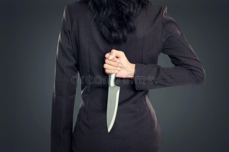 Mujer de negocios que retiene el cuchillo detrás el suyo imagenes de archivo