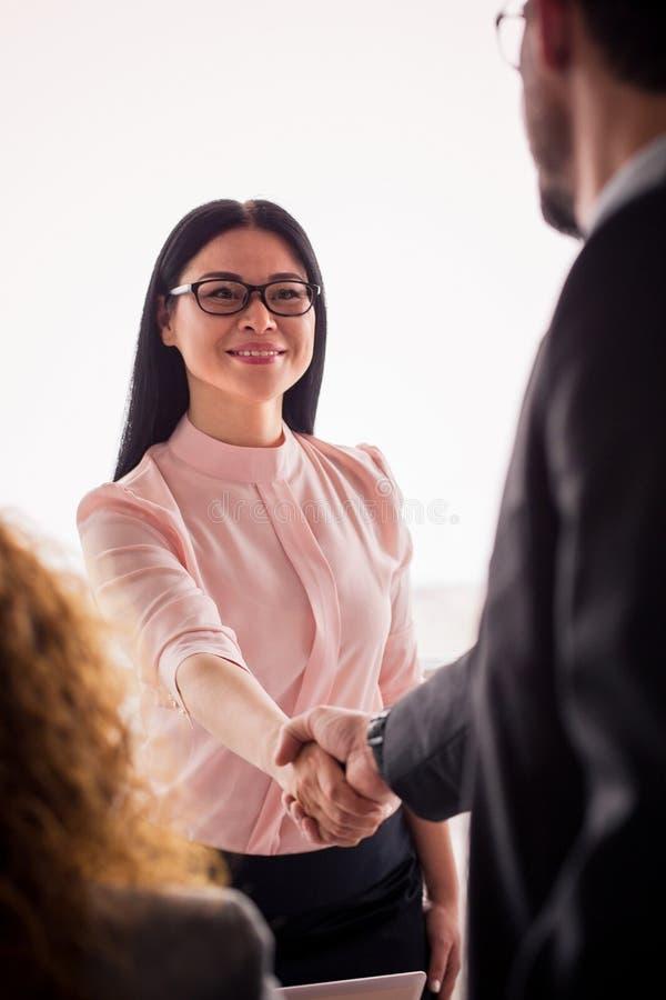 Mujer de negocios que sacude las manos con un socio foto de archivo