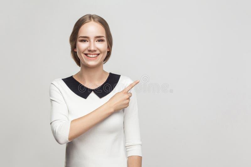 Mujer de negocios que señala el finger en el espacio de la copia, sonrisa dentuda y fotos de archivo libres de regalías