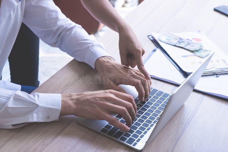 Mujer de negocios que señala en la pantalla del ordenador portátil, intercambio de ideas del compañero de trabajo foto de archivo